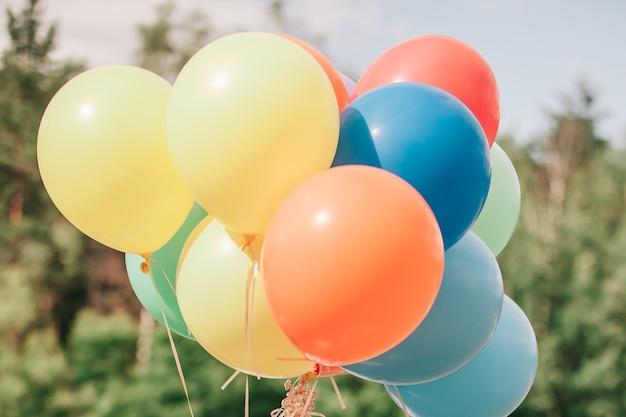 Ścieśniać. kilka kolorowych balonów na tle przyrody. zdjęcie z miejscem na kopię