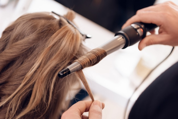 Ścieśniać. kobieta z brązowymi włosami robi zwijające włosy w salonie piękności