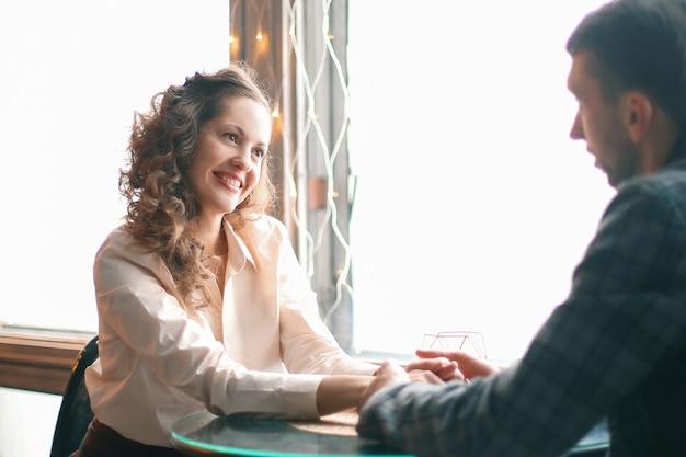 Ścieśniać. kochająca para siedzi przy stole w przytulnej kawiarni