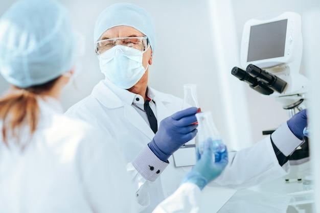 Ścieśniać. koledzy naukowcy dyskutują siedząc przy stole laboratoryjnym.