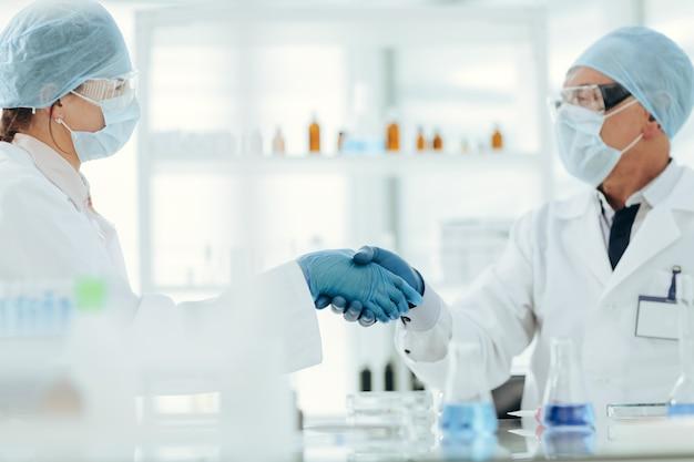 Ścieśniać. koledzy naukowcy ściskają sobie dłonie. nauka i zdrowie.