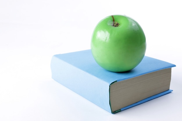 Ścieśniać. książka i zielone jabłko na białym tle.