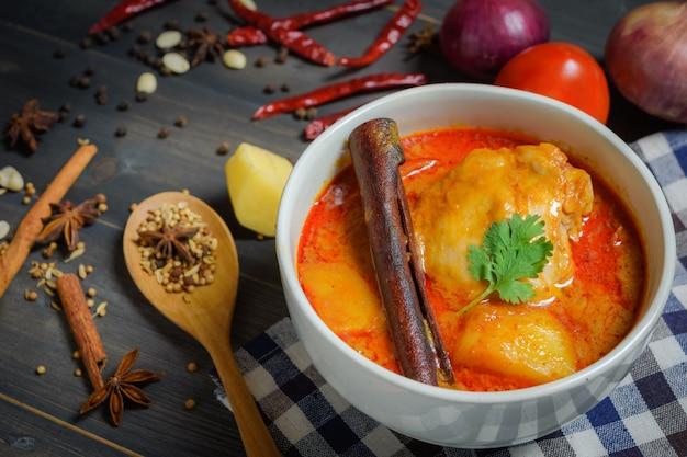 Ścieśniać kurczak massaman curry z zioła na drewnianym
