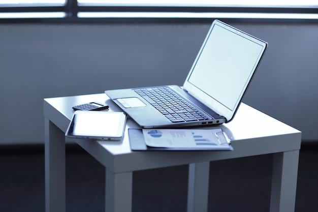 Ścieśniać. laptop i dokumenty finansowe na stole. pomysł na biznes