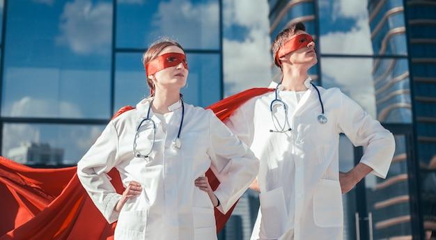 Ścieśniać. lekarze to superbohaterowie stojący na miejskiej ulicy. zdjęcie z miejscem na kopię.