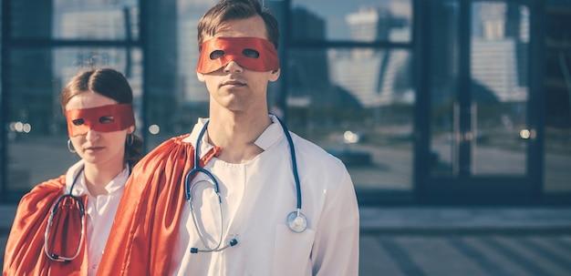 Ścieśniać. lekarze to superbohaterowie stojący na ulicy miasta. zdjęcie z miejscem na kopię.