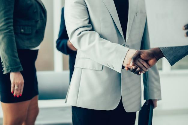 Ścieśniać. ludzie biznesu ściskają ręce, potwierdzając umowę. pojęcie współpracy