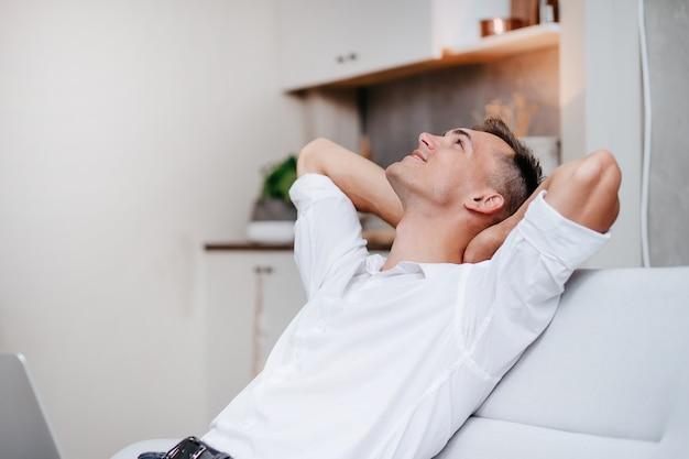 Ścieśniać. marzy młody człowiek z laptopem, siedząc na kanapie.