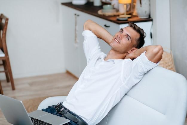 Ścieśniać. marzy młody człowiek z laptopem siedząc na kanapie.
