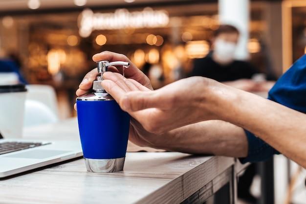Ścieśniać. mężczyzna dezynfekujący ręce siedzący przy stoliku w kawiarni. zdjęcie z przestrzenią do kopiowania