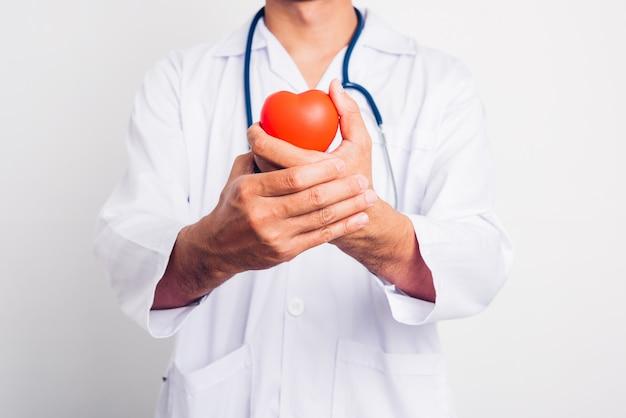 Ścieśniać mężczyzna lekarz ze stetoskopem trzyma pod ręką czerwone serce izolować na białym tle