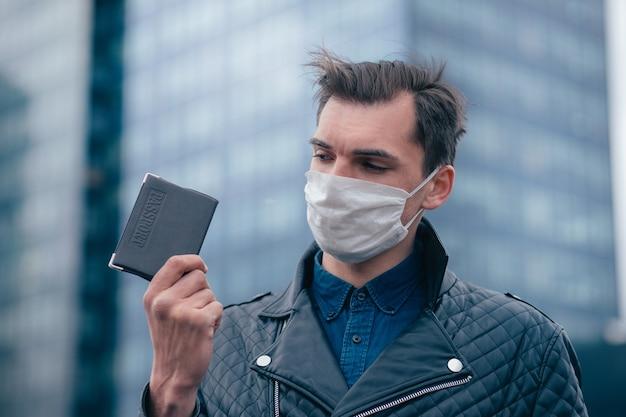 Ścieśniać. mężczyzna w masce ochronnej patrząc na paszport w dłoniach