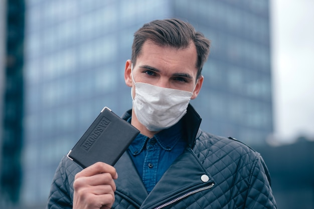 Ścieśniać. mężczyzna w masce ochronnej pokazujący paszport