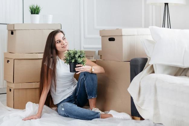 Ścieśniać. młoda kobieta marzy o tym, by usiąść na podłodze w nowym mieszkaniu