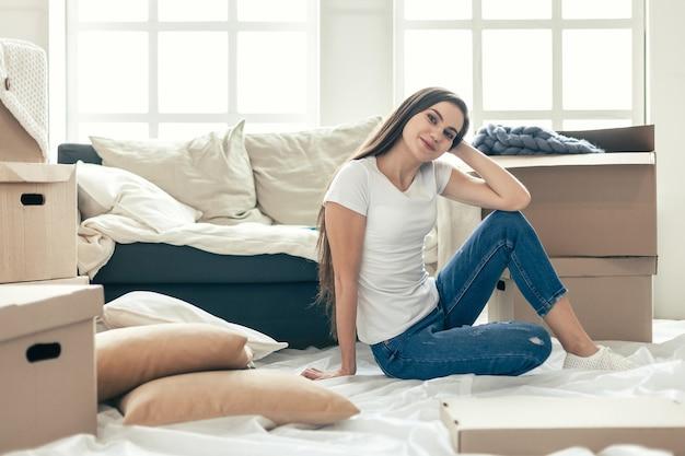 Ścieśniać. młoda kobieta patrząc na magazyn leżący w nowym salonie.