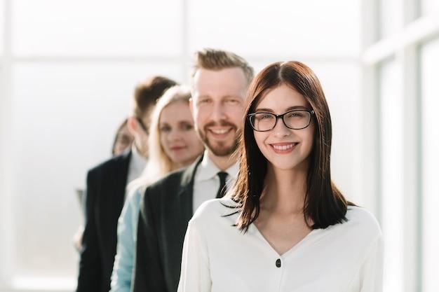 Ścieśniać. młoda kobieta stojąc przed zespołem biznesowym. pojęcie pracy zespołowej