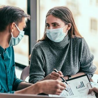 Ścieśniać. młoda kobieta w masce ochronnej rozmawia ze swoim kolegą.