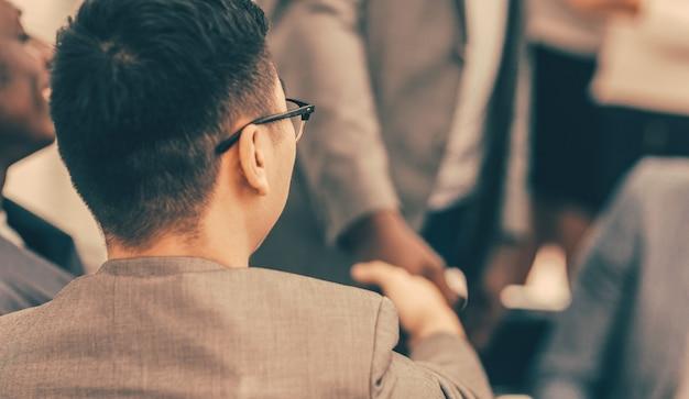 Ścieśniać. młody biznesmen komunikujący się z kolegami w biurze. widok z tyłu