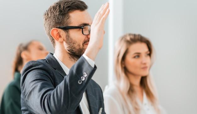 Ścieśniać. młody biznesmen zadaje pytanie podczas seminarium biznesowego. zdjęcie z miejscem na kopię