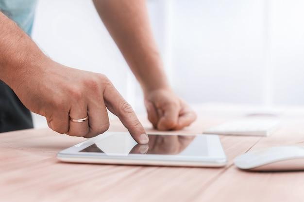 Ścieśniać. młody człowiek używa cyfrowego tabletu w biurze. ludzie i technologia