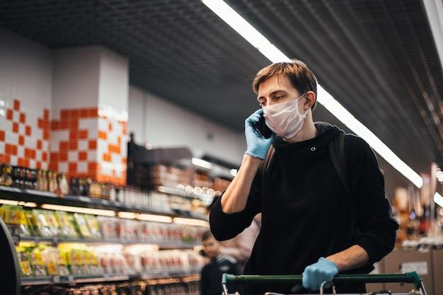 Ścieśniać. młody człowiek w masce ochronnej rozmawia na swoim smartfonie. higiena i opieka zdrowotna