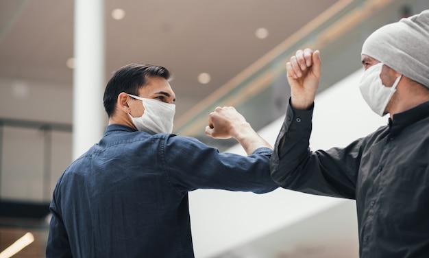 Ścieśniać. młody mężczyzna w masce ochronnej, witając przyjaciela