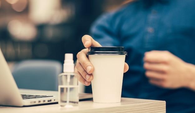 Ścieśniać. młody mężczyzna z kawą na wynos siedzący przy kawiarnianym stoliku