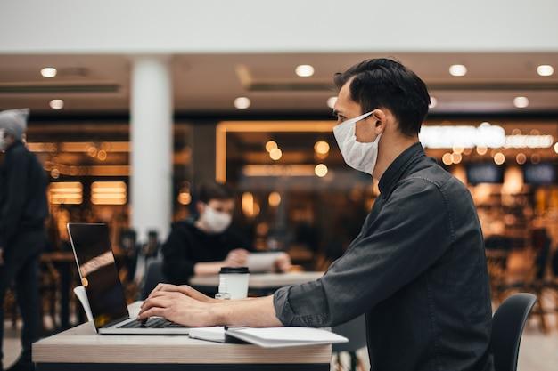 Ścieśniać. młody mężczyzna z laptopem pracuje przy stoliku w kawiarni