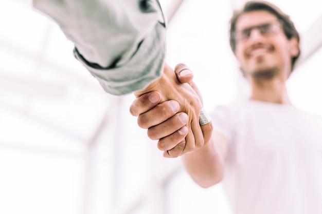 Ścieśniać. młody przedsiębiorca uścisk dłoni z partnerem biznesowym. koncepcja współpracy