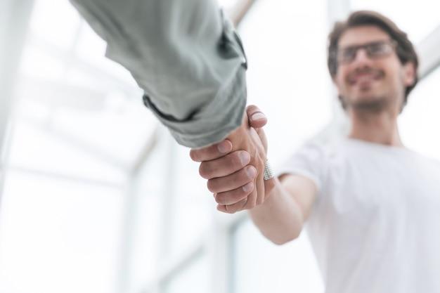 Ścieśniać. młody przedsiębiorca uścisk dłoni ze swoim partnerem biznesowym. koncepcja współpracy