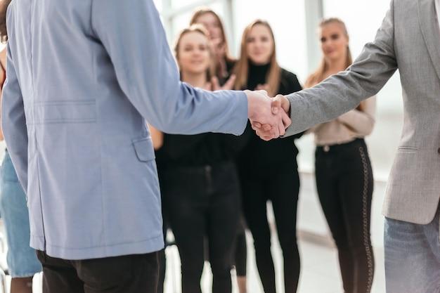 Ścieśniać. młodzi ludzie biznesu, ściskając ręce ze sobą. pomysł na biznes