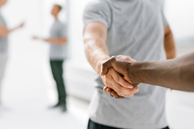 Ścieśniać. młodzi ludzie odnoszący sukcesy, ściskając ręce. zdjęcie z miejscem na kopię