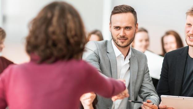 Ścieśniać. młodzi ludzie ściskają ręce na spotkaniu w biurze. koncepcja współpracy