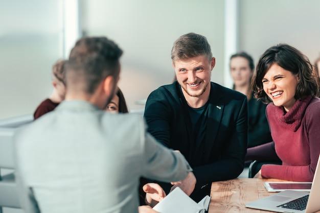 Ścieśniać. młodzi ludzie ściskają ręce na spotkaniu w biurze
