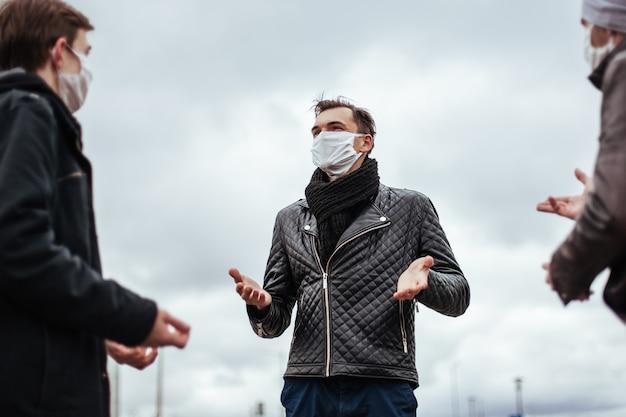Ścieśniać. młodzi ludzie w ochronnych maskach komunikują się na miejskiej ulicy