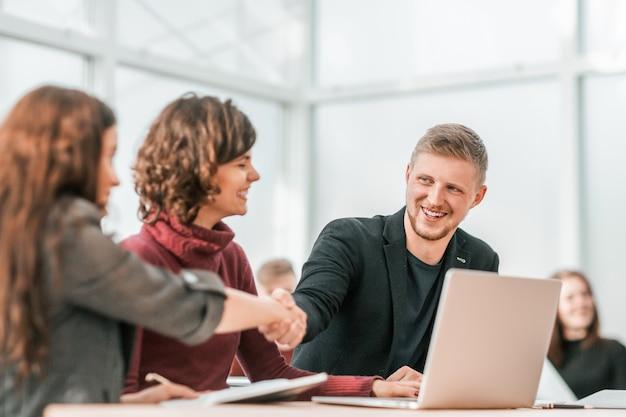 Ścieśniać. młodzi partnerzy biznesowi, ściskając ręce. koncepcja współpracy