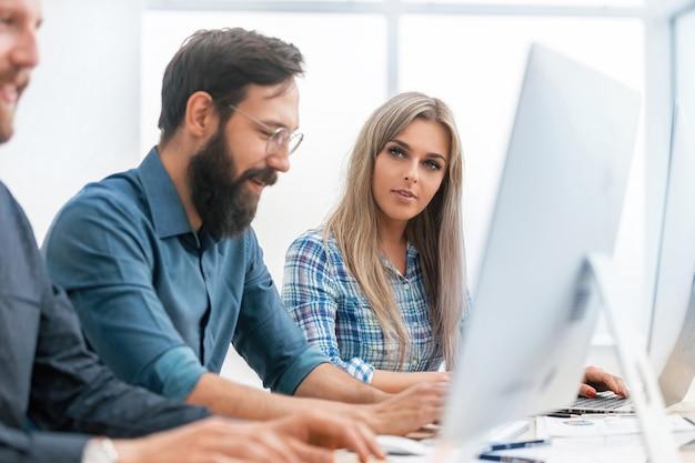 Ścieśniać. młodzi pracownicy pracują na komputerach osobistych w biurze. ludzie i technologia