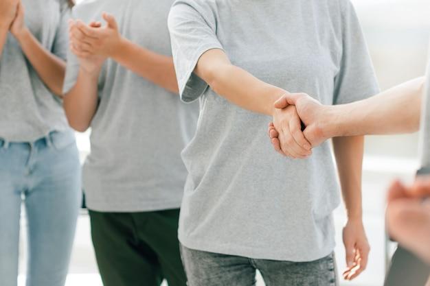 Ścieśniać. młodzi uczestnicy forum ściskają sobie dłonie