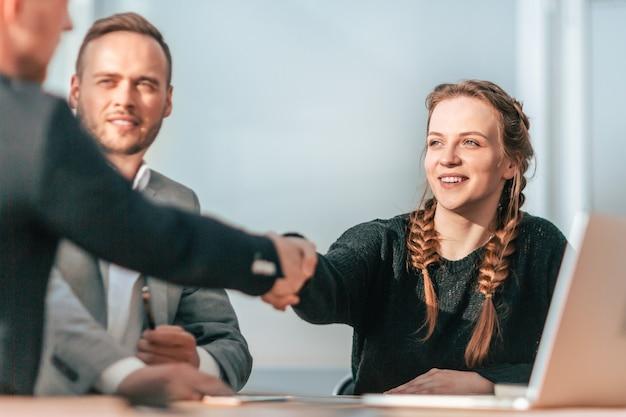 Ścieśniać. młodzi współpracownicy ściskają sobie dłonie na spotkaniu grupowym.