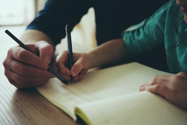 Ścieśniać. nastolatek dziewczyna pisze piórem w notatniku.