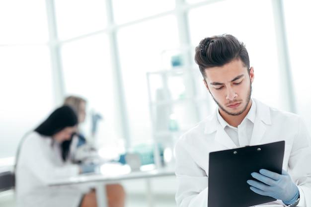Ścieśniać. naukowiec, który prowadzi badania, zapisuje wyniki eksperymentu w dzienniku laboratoryjnym. zdjęcie z miejsca na kopię