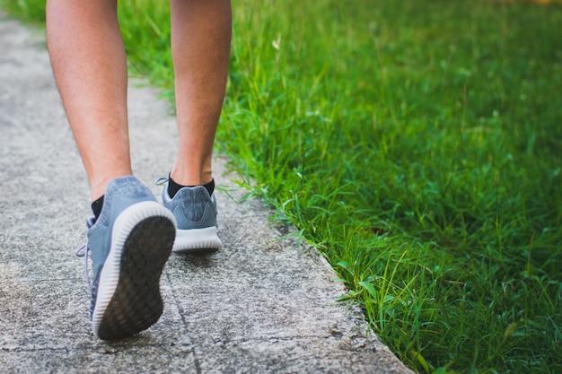 Ścieśniać. noga. człowiek z biegaczem na ulicy biegać do ćwiczeń. przydrożna łąka