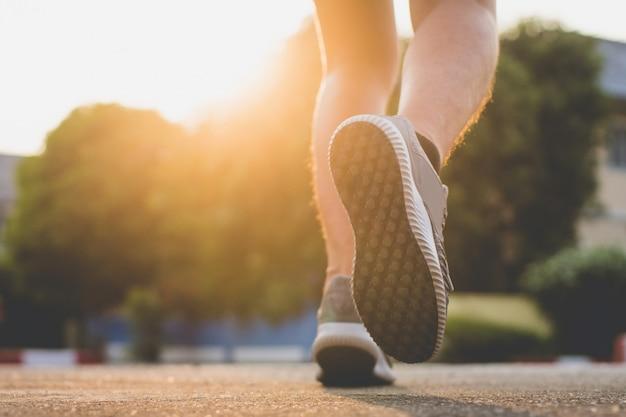 Ścieśniać. noga. światło słoneczne. człowiek z biegaczem na ulicy biegać do ćwiczeń