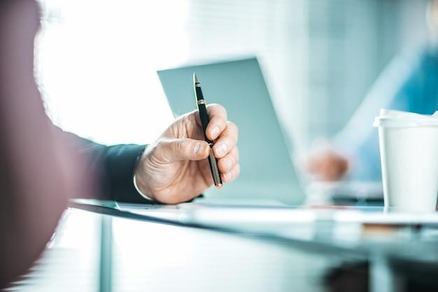 Ścieśniać. obraz w tle biznesmena siedzącego w pobliżu pulpitu. zdjęcie z miejscem na kopię