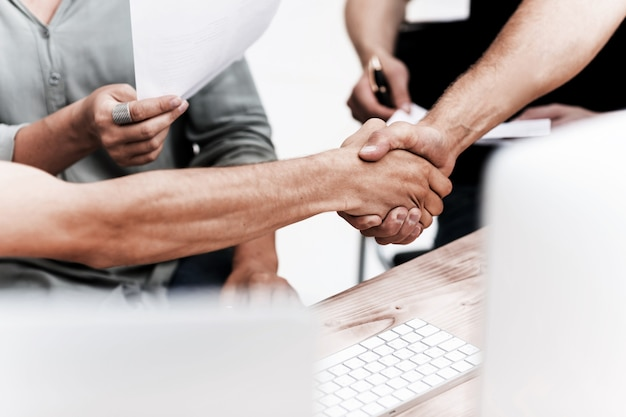 Ścieśniać. obraz w tle przyjaznego uścisku dłoni pracowników. zdjęcie z miejscem na tekst