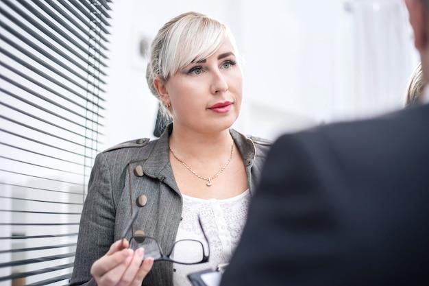 Ścieśniać. odnosząca sukcesy bizneswoman wyjaśniając coś swojemu koledze. ludzie biznesu