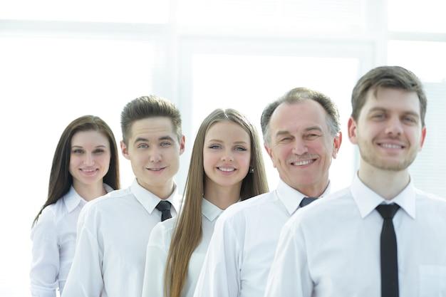 Ścieśniać. odnosząca sukcesy grupa pracowników stojących w rzędzie. koncepcja pracy zespołowej
