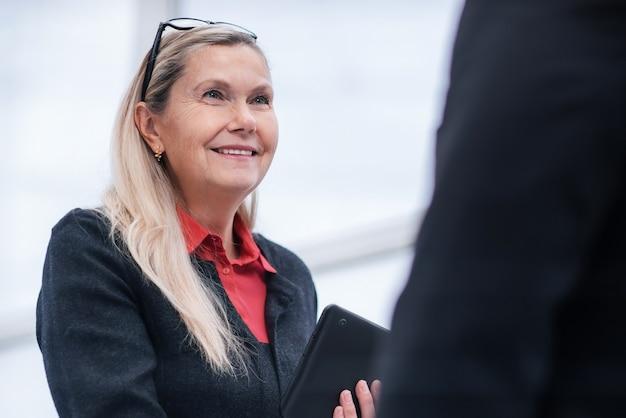 Ścieśniać. odpowiedzialna kobieta biznesu rozmawia z kolegami. biurowe dni powszednie
