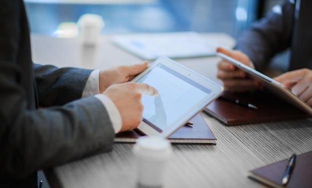 Ścieśniać. partnerzy biznesowi z cyfrowymi tabletami omawiają nowy kontrakt . pomysł na biznes.