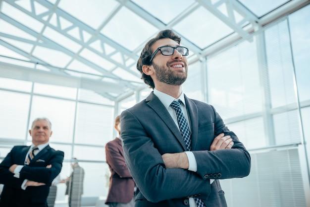 Ścieśniać. pewny siebie biznesmen stojący w nowoczesnym biurze